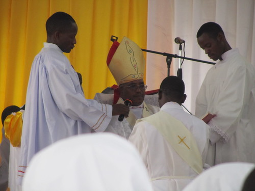 The Bishop blessing the new priest.