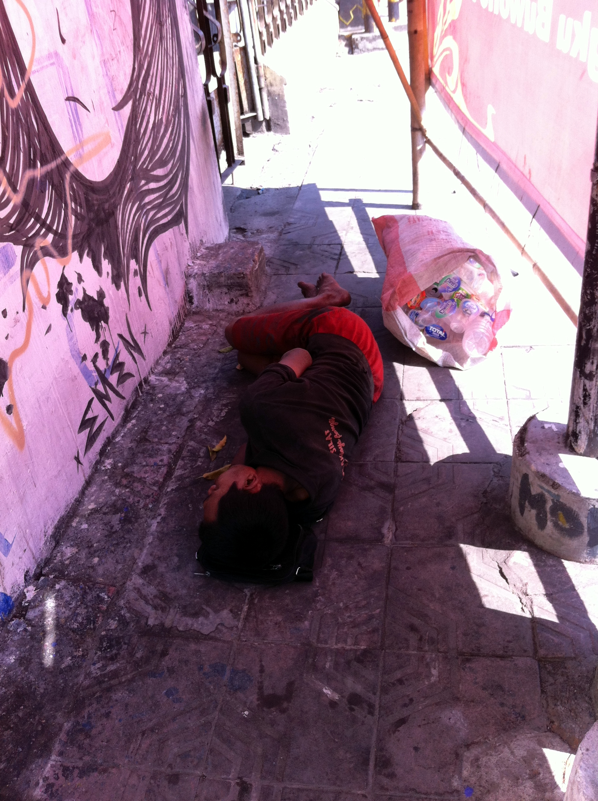A plastic bottles collector sleeping on the sidewalk