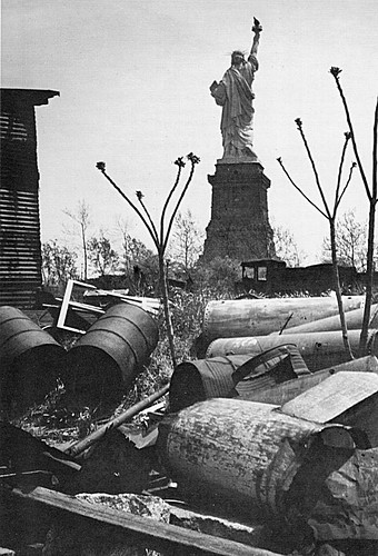 Yet another bleak industrial wasteland at the Black Tom part of Jersey City toward the Statue of Liberty with rusting chemical drums and asbestos coated pipes.  Right about where the circle of flags is now in Liberty State Park. 1970