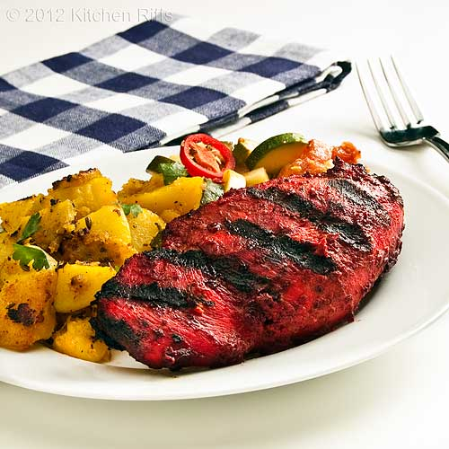 Tandoori Chicken on Plate with Spicy Potatoes and Summer Squash in Tomato Curry Sauce