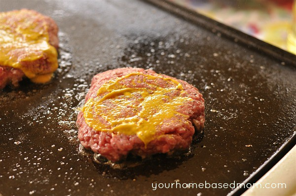 hamburger on a grill topped with mustard