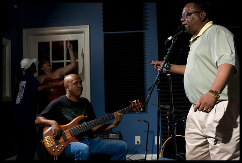 Caesar Elloie sings, with Anthony Hamilton on guitar.  WWOZ's Dee and Crystal are dancing in the background.  Photo rhrphoto.com