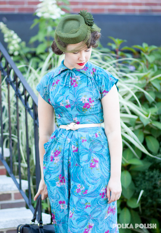 A vintage 1940s tilt hat picks up olive green tones from a novelty print vintage dress with bows and flowers