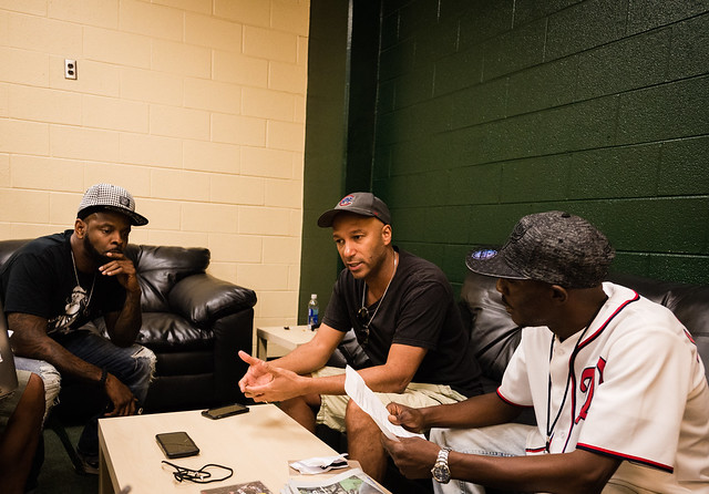 A photo of DJ Lord and Tom Morello interviewing with Ronald Dudley.