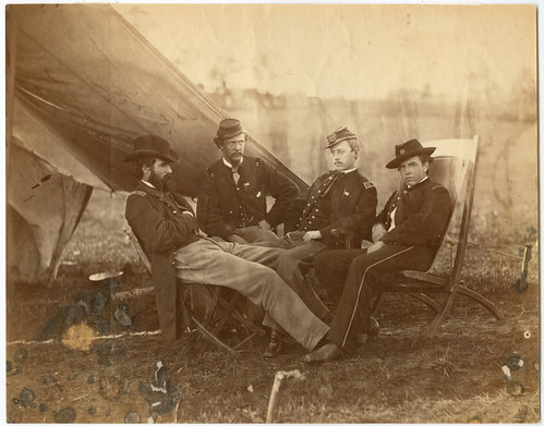 [Four Union soldiers seated in chairs near a tent]