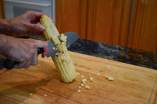 A knife cutting the grilled corn off it's cob.