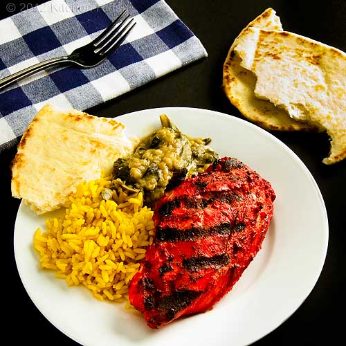 Tandoori Chicken on Plate with Dal, Rice, and Naan, Black Background