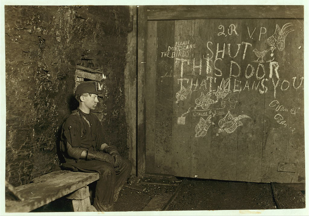 Vance, a Trapper Boy, 15 years old. Has trapped for several years in a West Va. Coal mine. $.75 a day for 10 hours work. All he does is to open and shut this door: most of the time he sits here idle, waiting for the cars to come.