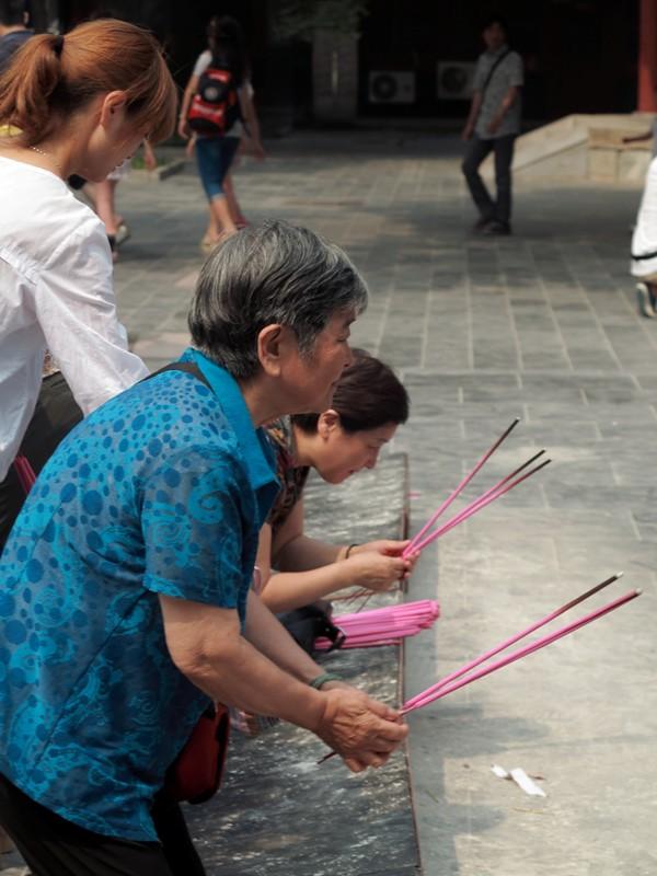 Croyante brulant de l'encens au temple des Lamas