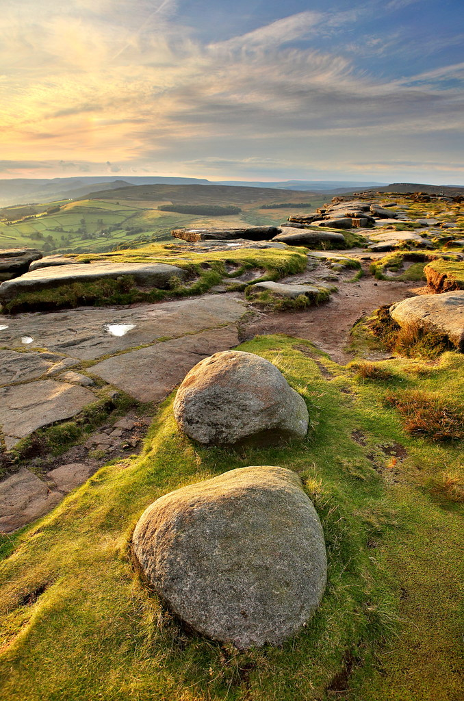 Golden sunset light over stanage edge in the peak district, lighting up the rocks of the dark peak