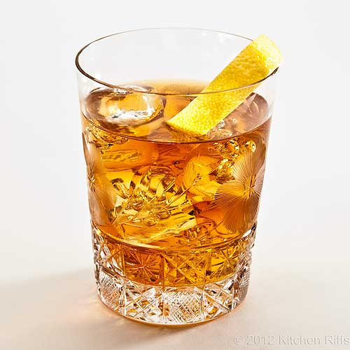 Old-Fashioned Cocktail in Crystal Rocks Glass with Lemon Twist Garnish, White Background