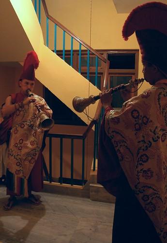 Tibetan Buddhist monks blow horns announcing the arrival of the young lama prince, HE Asanga Sakya, Sakya Lamdre, traditional garments, stairwell, Tharlam Monastery of Tibetan Buddhism, Boudha, Kathmandu, Nepal by Wonderlane