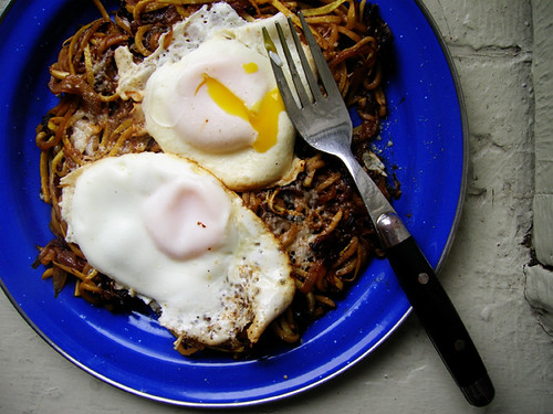 fried eggs and summer squash noodles with caramelized onions