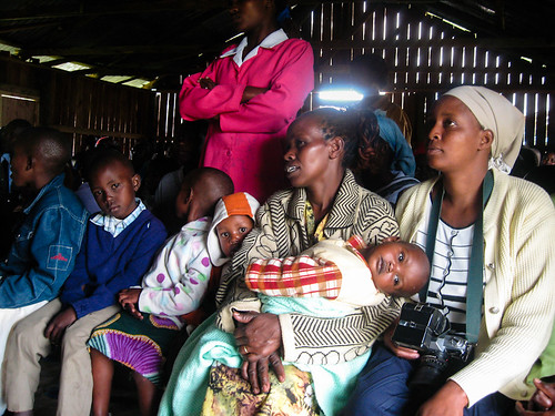 Church members learn about HIV/AIDS from a community health worker while distracted children stare out the door. A local journalist sits with her camera, ready to record the days' events. Great Rift Valley Region, Kenya