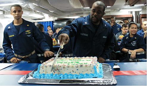 USS Higgins sailors look on as Petty Officer Third Class Tomarcus Armstrong cuts a cake celebrating Dr. Martin Luther King Jr.