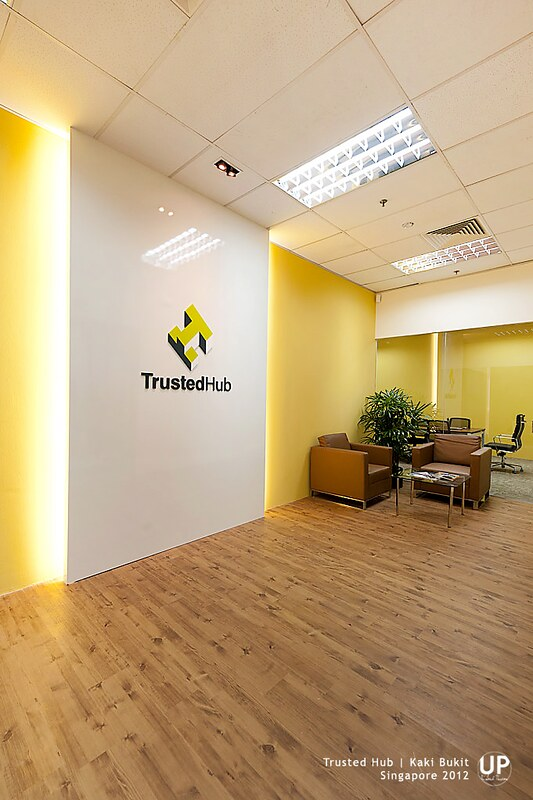 Office Entrance with yellow highlight wall, signage panel with concealed light, showing waiting lounge and conference room at the far end