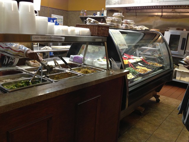 Angled shot of an open hot bar and a covered deli case full of food.