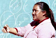Domitila Barrios de Chungara speaking in pink sweater in front of chalkboard