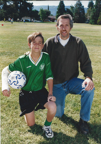 Boy#1 with a cast on his arm in his soccer uniform kneeling next to his dad.