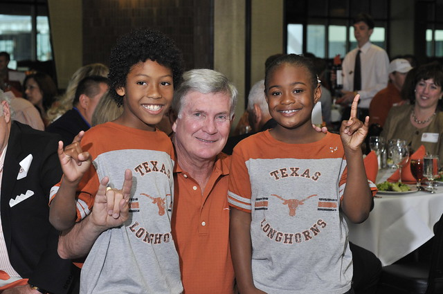 Mack Brown with kids doing Hook Em'