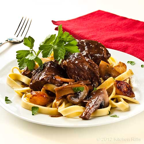 Boeuf Bourguignon on Plate with Mushrooms and Homemade Noodles and Parsley Garnish