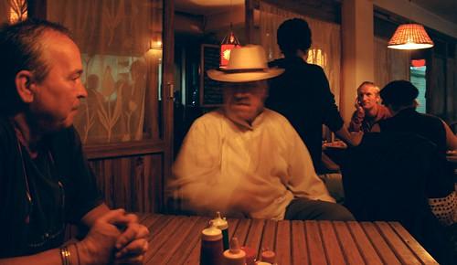 Sangha chatting about Buddhism at the Toast Bakery, Steve D., Tashi,  Paul Hatton of Australia, other prostrators taking a break to eat, night waiting for dinner, Boudha, Kathmandu, Nepal by Wonderlane