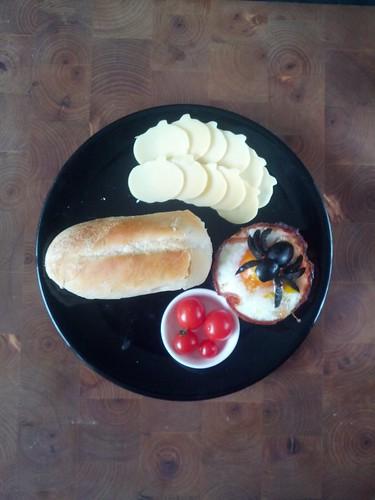 Een foto van bovenaf van een zwart bord op een donkere houten actergrond Op het bord staat een ei in een bakje van bacon met een spin gemaakt van zwarte olijf er bovenop. Naast het ei staat een schaaltje met mini-kerstomaten, een rij pompoenvormige kaasplakjes en een pistoletje.