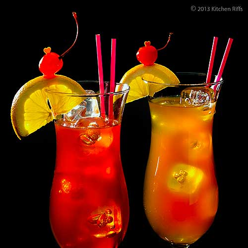 Two Hurrican Cocktails in Hurricane Glasses with Orange and Cherry Garnish