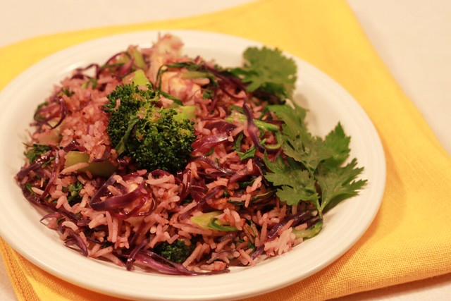 Plate of purplish-pink fried rice with cabbage, broccoli, and cilantro on the side.