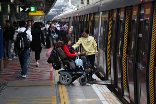 MTR staff assist a wheelchair bound passenger onboard a train