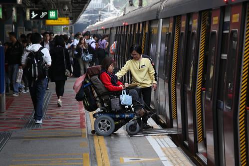 MTR staff assist a wheelchair bound passenger onboard a train