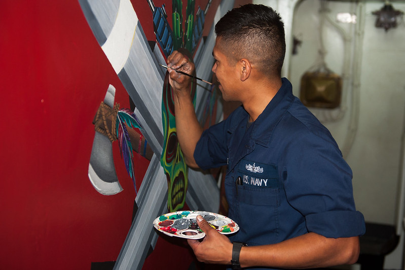 Gunner's Mate Seaman Daniel Hernandez paints a mural to represent the weapons department.