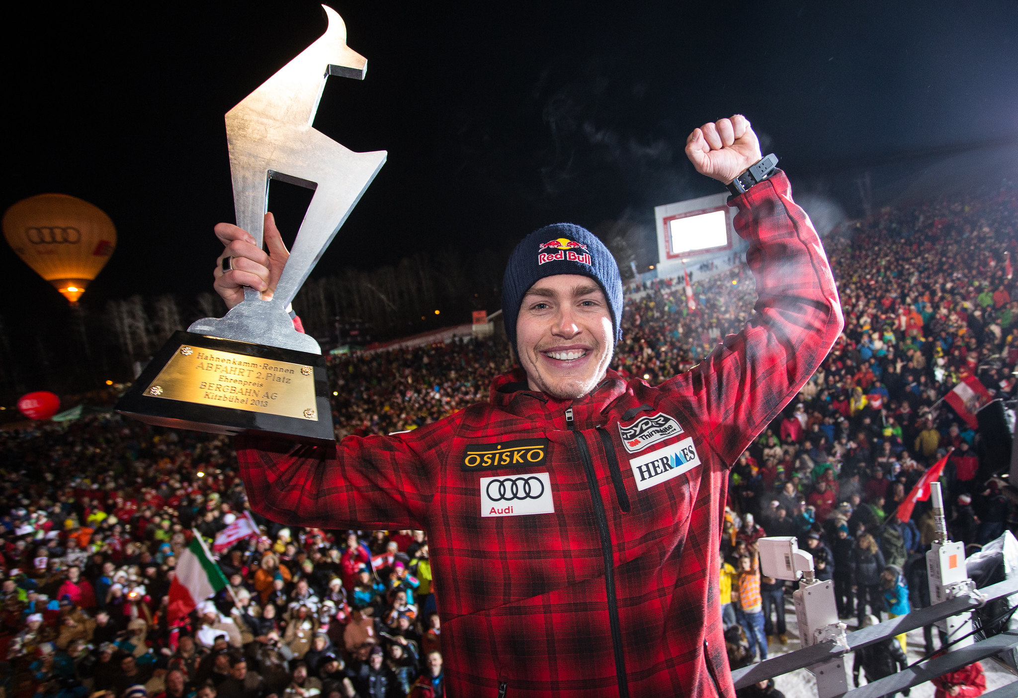 Erik Guay hoists his second-place trophy to a cheering crowd at the nighttime awards ceremony for the men's downhill in Kitzbühel, Austria.