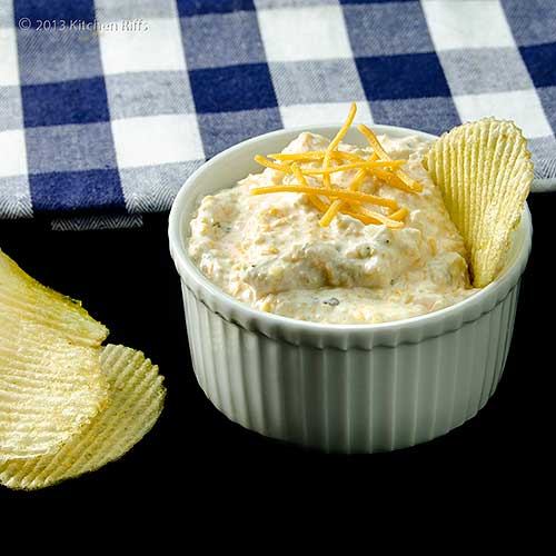 Artichoke Dip with Cheddar Cheese in White Ramekin with Potato Chips
