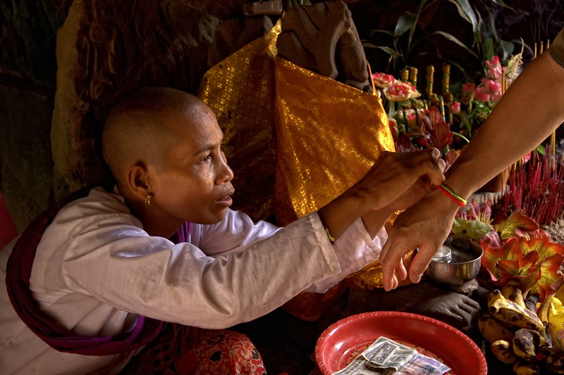 A Buddhist Nun Ties A String Of Faith, Cambodia