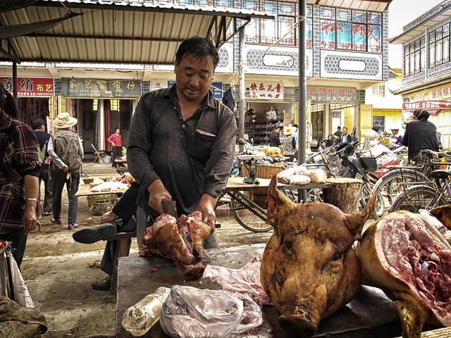 Burcher cutting pork head