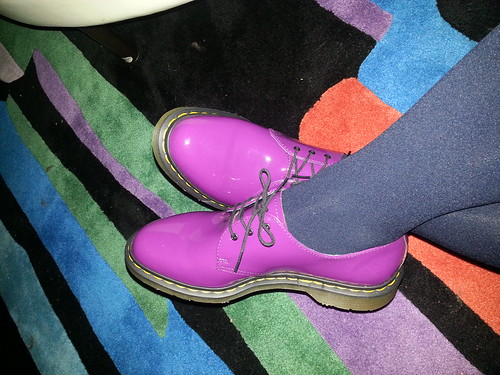 A pair of magenta Doc Martens oxfords against a multi-colored rug