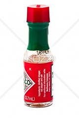 small bottle of a pepper sauce bottle on white bac…
