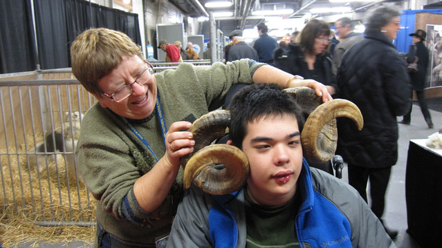 Judy Miller-Shelley placing ram horns on the sides of Jon's head