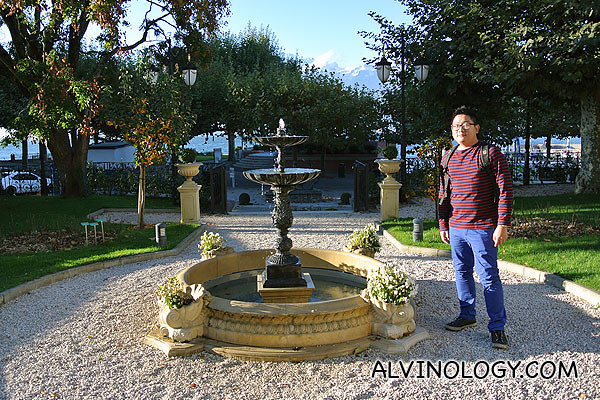 Me standing beside a fountain just in front of the hotel facing Lake Geneva