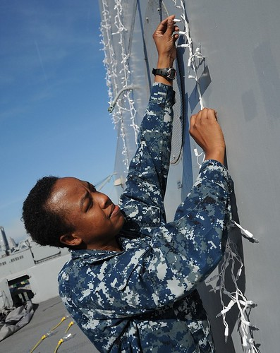 Electrician's Mate 3rd Class Adella Atwell affixes holiday lights to the aft of (PCU) Anchorage