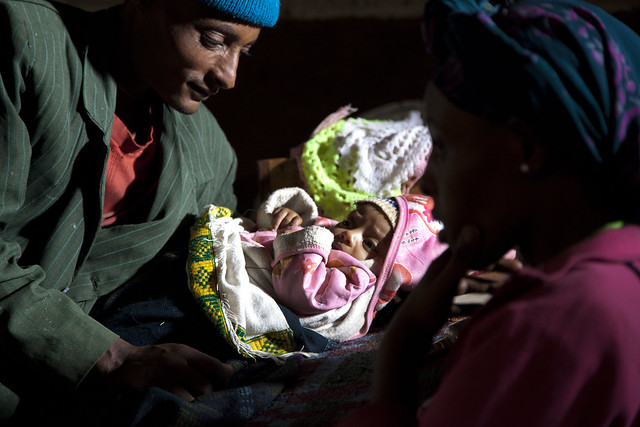 Kokeb Negussie and her husband Teshome watch their two month old son Moges rest in Romey Village-Amhara Region