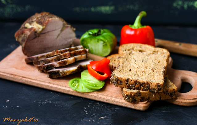 Baked pork loin with garlic and vegetables, whole wheat bread with seeds