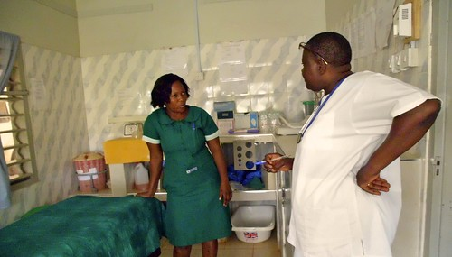Esther Adzah SSL in a conversation with a nurse in the maternity room at St John's Health Centre, Domeabra, Ghana
