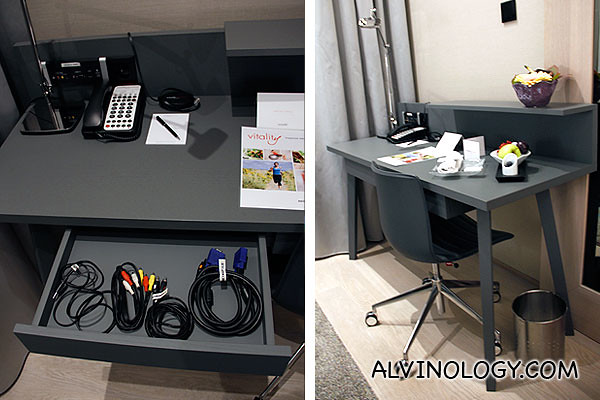 A work area in the room with a drawer containing all sorts of cables