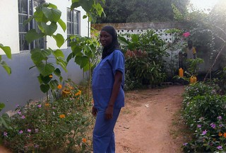 Expectant Aja Bojang, Midwife, in the clinic garden.