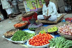 Fruits and vegetables are offered for sale  at an open-air market.