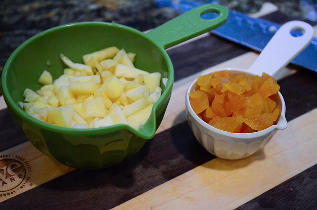 Measuring cups with apple and dried apricots.