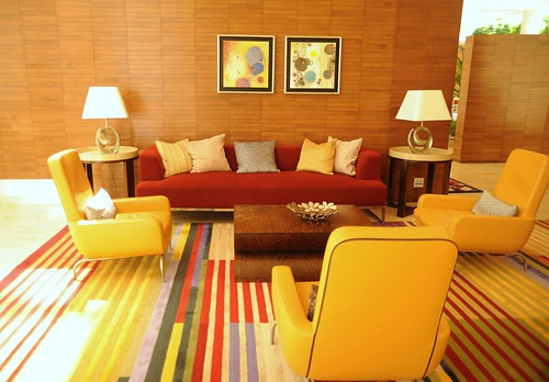 Lounge room, sofas, pillows, armchairs, end tables, lamps, art, wood walls, striped carpet, red and yellow, contemporary furniture, Renaisance Hotel, Schaumburg, Illinois, USA