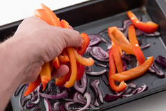 Human hand adding sliced bell pepper to sliced red…